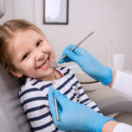Little girl smiles while sitting in the dentist chair in Pharr, TX