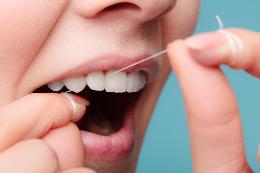 Closeup of a woman flossing her teeth because it is important