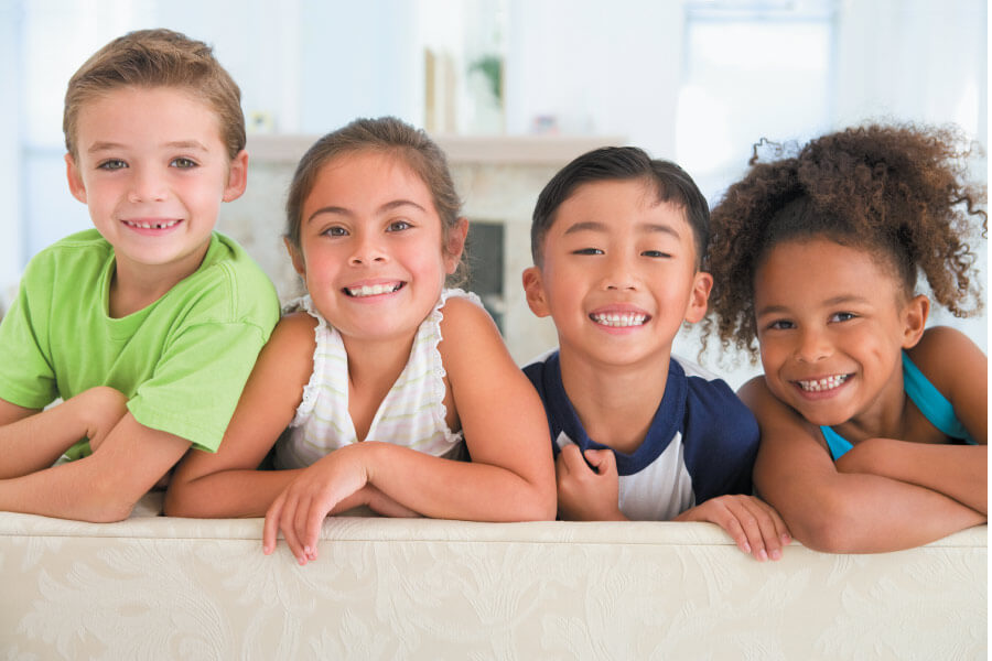 A group of children smile after receiving a fluoride treatment at the dentist in Pharr, TX